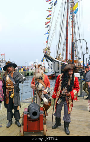 Halifax, Nova Scotia, Canada - July 29, 2017:  Members of the Pirates of Halifax troupe pose with tourists in front - Stock Photo