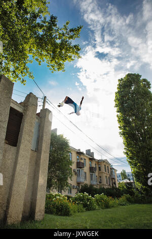 City parkour. The guy does the opposite somersault. Leap from the building. Shooting from the lower angle. Dexterity - Stock Photo