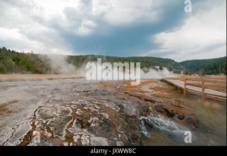 Mist and vapor rising off Hot Cascades hot spring in the Lower Geyser Basin in Yellowstone National Park in Wyoming - Stock Photo