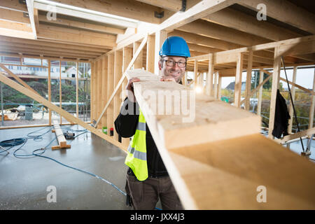 Portrait Of Confident Mature Carpenter Carrying Wood - Stock Photo