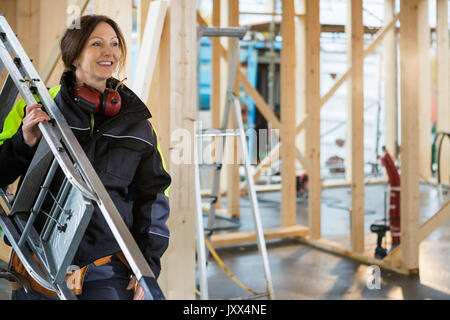 Female Carpenter Carrying Ladder At Construction Site - Stock Photo