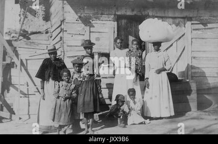Full length portrait of an African American family: one mature woman wearing a hat and dress, three young girls - Stock Photo