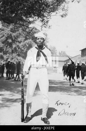 Portrait of an African American US Navy Sailor standing in front of two groups of sailors practicing in dark colored - Stock Photo
