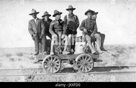An African American man and a couple white men are sitting and standing on a handcar that is on a railroad track, - Stock Photo