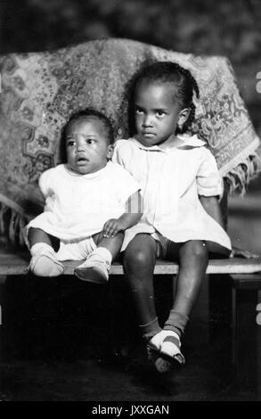 Full portrait, two African American children--one baby, and another older girl, seated, looking in different directions, - Stock Photo