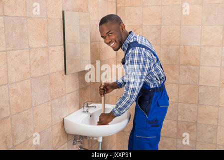 Happy Young African Male Plumber Using Plunger In Bathroom Sink - Stock Photo