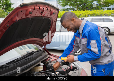 Happy Mechanic Using Multimeter To Check The Voltage Level In A Car Battery - Stock Photo
