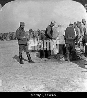 Hungrige Soldaten sammeln sich an dampfenden Kesseln einer Feldküche an der serbischen Front, 1910er Jahre. Hungry - Stock Photo