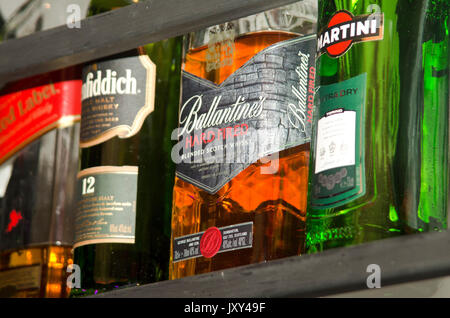 various bottles of alcohol on display in a bar - Stock Photo