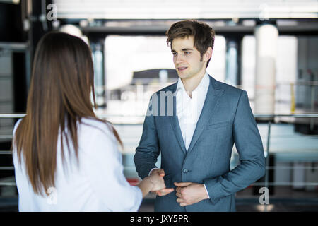 Business men and women talking with a smile on the background of the large panoramic windows in a modern business - Stock Photo