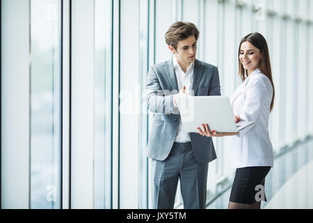 Businessman and businesswoman using a laptop together while standing in front of office building windows - Stock Photo