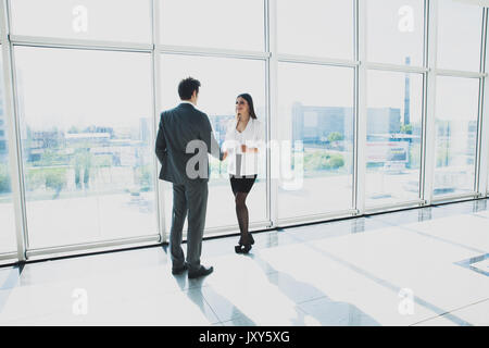 View from below of two young businessmen are standing in modern office with panoramic windows. - Stock Photo