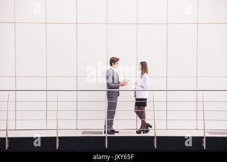 Confident business partners walking down in office building and talking - Stock Photo