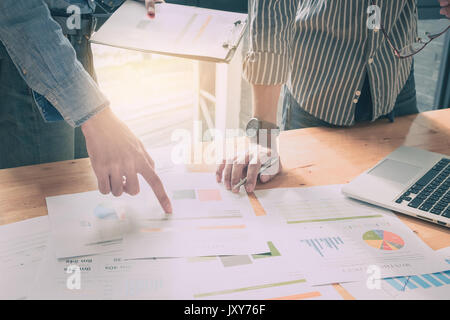 Close up of business man hand pointing at business document on financial paper during discussion at meeting. Group - Stock Photo