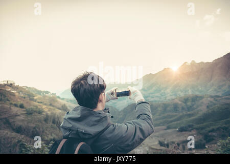 traveler photographing mountain and sun and sky by smartphone. - Stock Photo