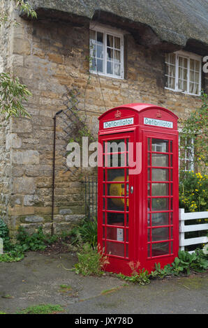 Old red telephone kiosk in the village of Geddington, now used as a defibrillator unit, part of the BT Adopt A Kiosk - Stock Photo