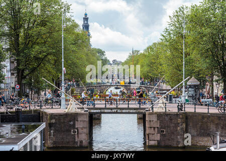 Amsterdam the Netherlands - 13 August 2017: people crossing bridges on the Prinsengracht with westerkerk in background - Stock Photo