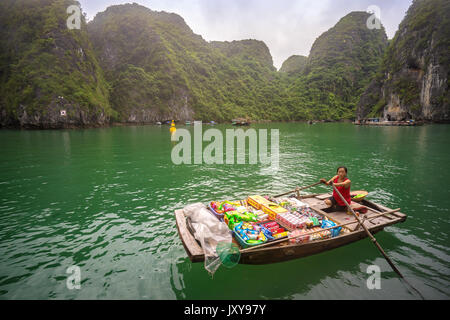 traditional vietnamese boat vendor selling products on a junk boat in Halong Bay, Vietnam - Stock Photo