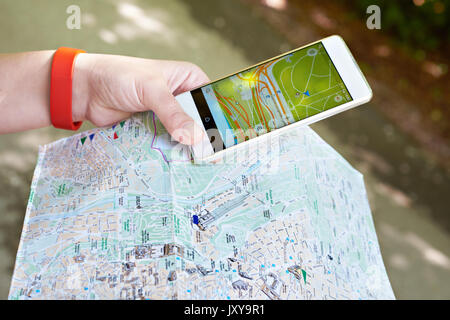 Smartphone with GPS navigator and map in the hands of a tourist - Stock Photo