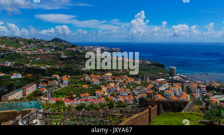 Madeira - Fisherman village camara de Lobos from Miradouro de Torre with blue ocean and houses and industry - Stock Photo