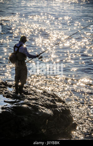 A man heads out fishing early early in the morning while the tide is high,and the sun reflects off the small waves - Stock Photo