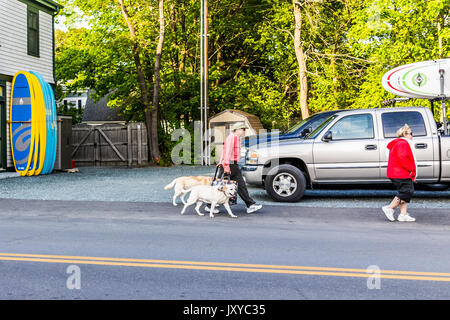 Bar Harbor, USA - June 8, 2017: Happy people crossing sidewalk street in downtown village in summer on main road - Stock Photo