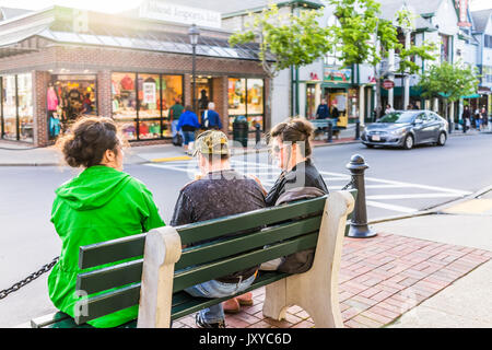 Bar Harbor, USA - June 8, 2017: People on benches in Maine downtown village in summer evening eating ice cream - Stock Photo
