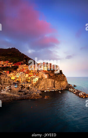 Manarola at sunset.  One of the five towns of the Cinque Terre, the cliff town of Manarola is perched along the - Stock Photo