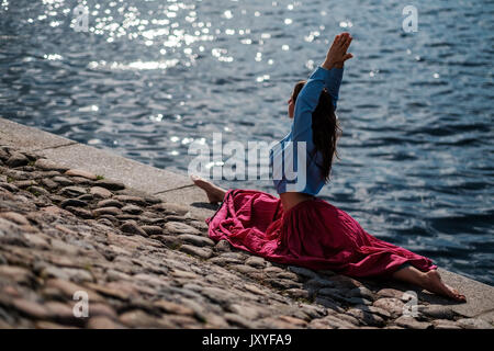 Sporty fit caucasian woman doing asana Virabhadrasana 2 Warrior pose posture in nature. - Stock Photo