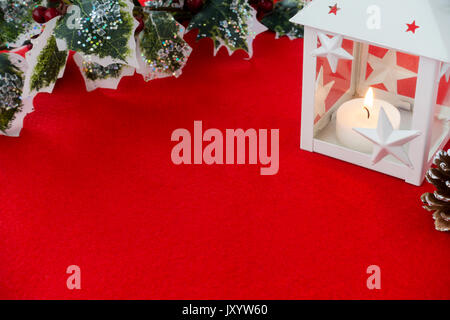 White Christmas lantern with lit candle, holly branch decorated with glitter and glass stones and a pine cone on - Stock Photo