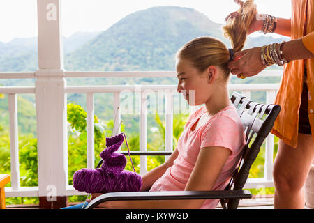 Caucasian mother holding ponytail of daughter - Stock Photo