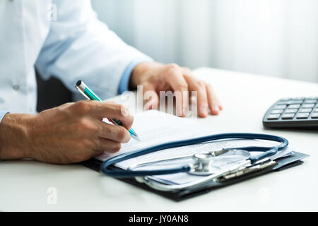 doctor writing prescription at desk in clinics office - Stock Photo