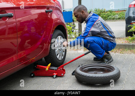 Young African Mechanic Changing Tire Of A Red Car With Wrench - Stock Photo