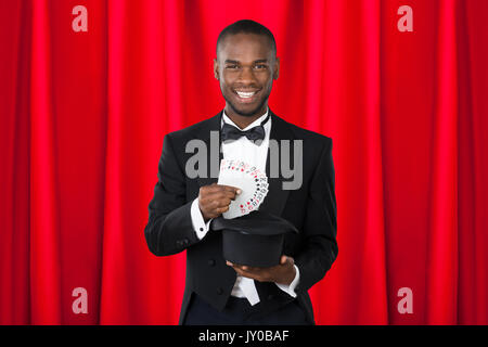 Young Happy Magician Showing Trick With Playing Cards - Stock Photo