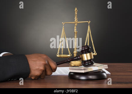 Close-up Of A Judge Striking The Gavel On Banknote At Desk - Stock Photo