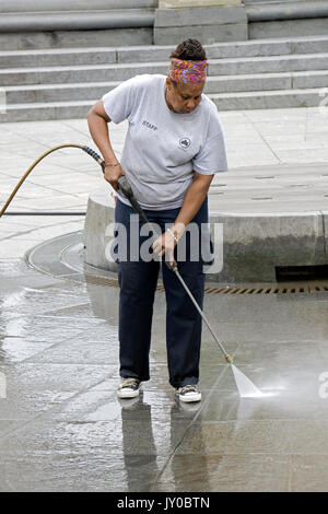 A New York City Parks Dept. worker power washing the fountain area in Washington Square Park in Greenbwich Village, - Stock Photo
