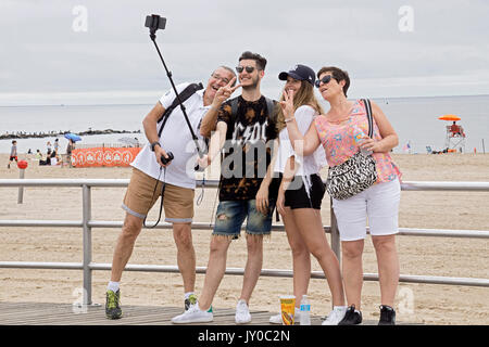 A tourist family visiting Coney Island in Brooklyn take a selfie on the boardwalk facing the Atlantic Ocean. - Stock Photo
