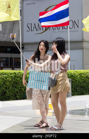 Chinese tourists taking a selfie outside Siam Paragon with Thai flag, Bangkok, Thailand - Stock Photo