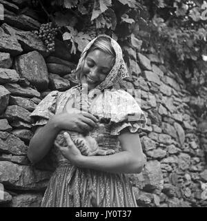 Young woman in peasant dress hugging kitten. - Stock Photo