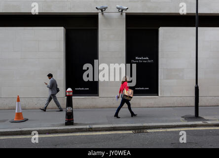 Londoners walk beneath two CCTV cameras in the City of London, one of the most-watched  on 11th August, 2017, in - Stock Photo