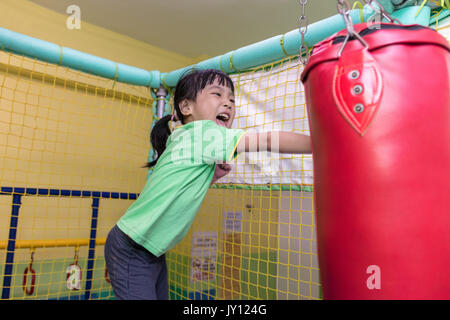 Asian Chinese little girl playing with punching bag at indoor playground - Stock Photo