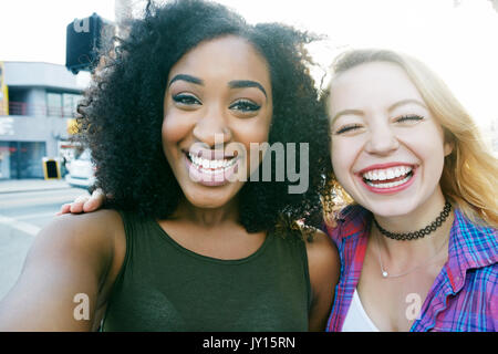 Friends posing for selfie in city - Stock Photo