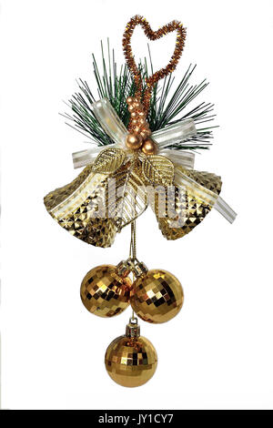 Golden christmas decoration - two bells with bow, golden leaves, green branch of fir tree and three baubles close - Stock Photo