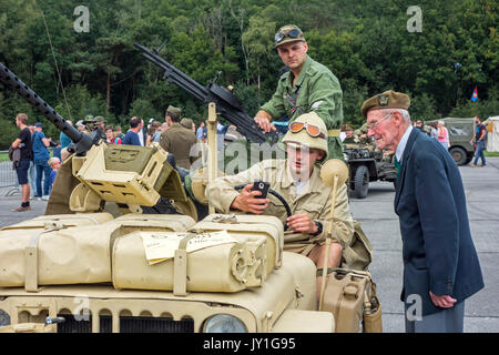 Elderly war veteran talking to young WW2 reenactors in WWII jeep with mounted Vickers K machine gun during World - Stock Photo