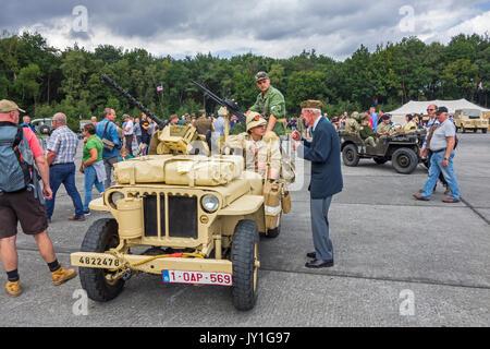 Elderly war veteran talking to young WW2 reenactors in WWII SAS Willys MB jeep during World War Two militaria fair - Stock Photo