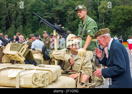 Elderly war veteran talking to young WW2 reenactor in WWII jeep with mounted Vickers K machine gun during World - Stock Photo