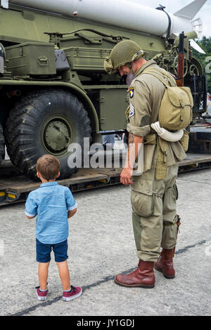 Little boy and WW2 reenactor in US soldier outfit looking at missile truck at World War Two militaria fair - Stock Photo