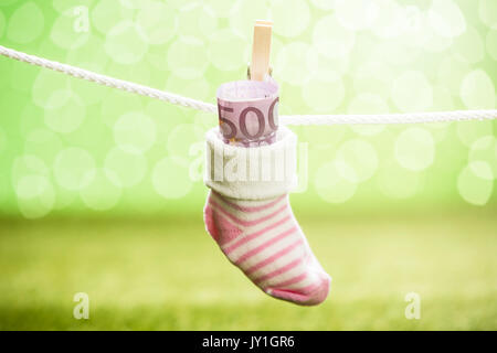 Baby Sock With Dollar Hanging On Rope Using Wooden Clip - Stock Photo