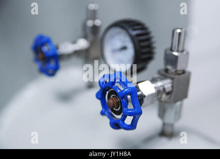 Closeup of pressure gauge and blue valve - Stock Photo