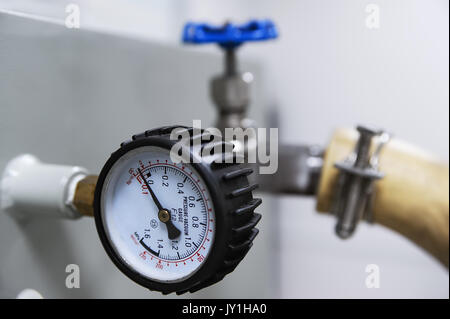 Closeup of pressure vacuum gauge and blue valve - Stock Photo